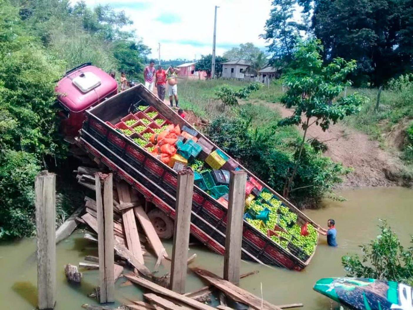 Caminhão, em área rural, carregado de alimentos perecíveis caído em um um rio por causa de quebra de ponte de madeira